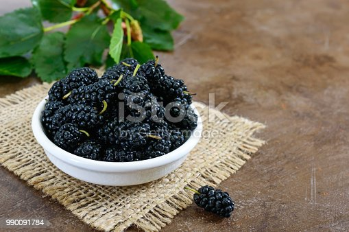 istock Ripe black mulberry in a bowl. Close-up. 990091784