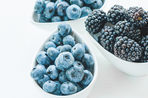 840939766 istock photo Ripe blueberries and blackberries on white background in white ceramic bowls. Close up. 926692228