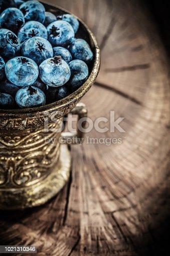 Ripe blueberries in vintage metal bowl on grunge board.