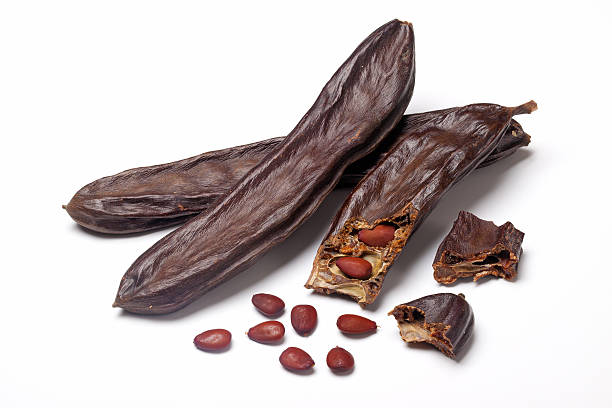 Ripe carob on white background  stock photo
