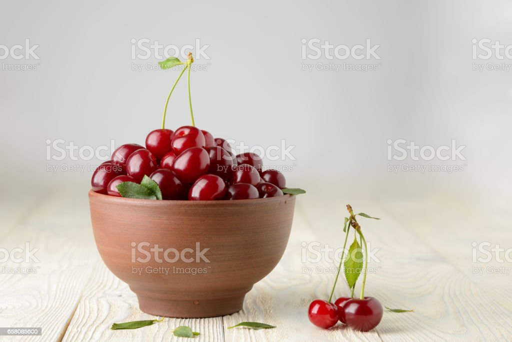 ripe cherries and leaves in a bowl on a textured wooden background royalty-free stock photo