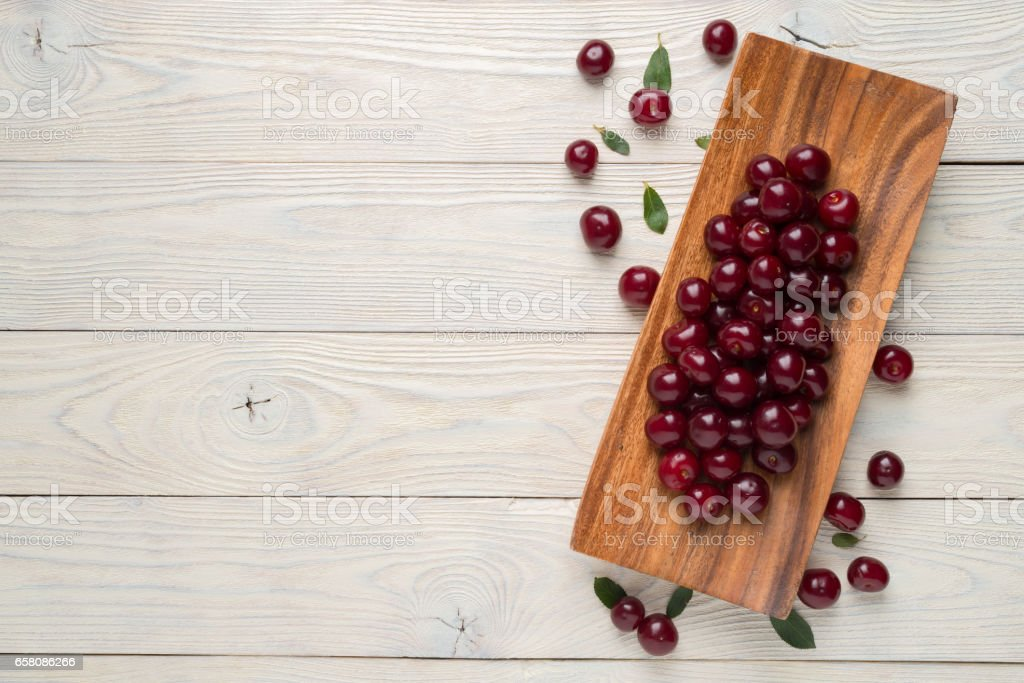 ripe cherries and leaves in a dish on a textured wooden background, view from above royalty-free stock photo