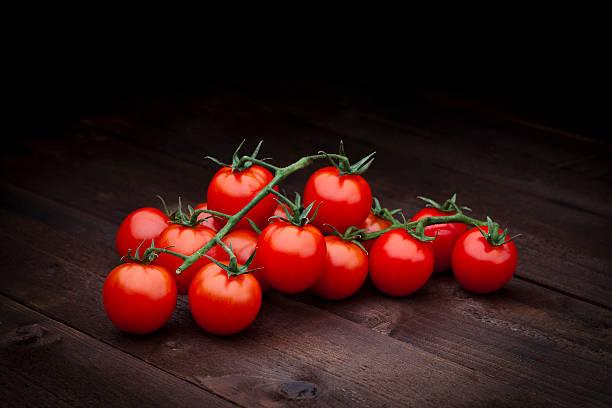 ripe cherry tomatoes on dark wood background - negras maduras fotografías e imágenes de stock