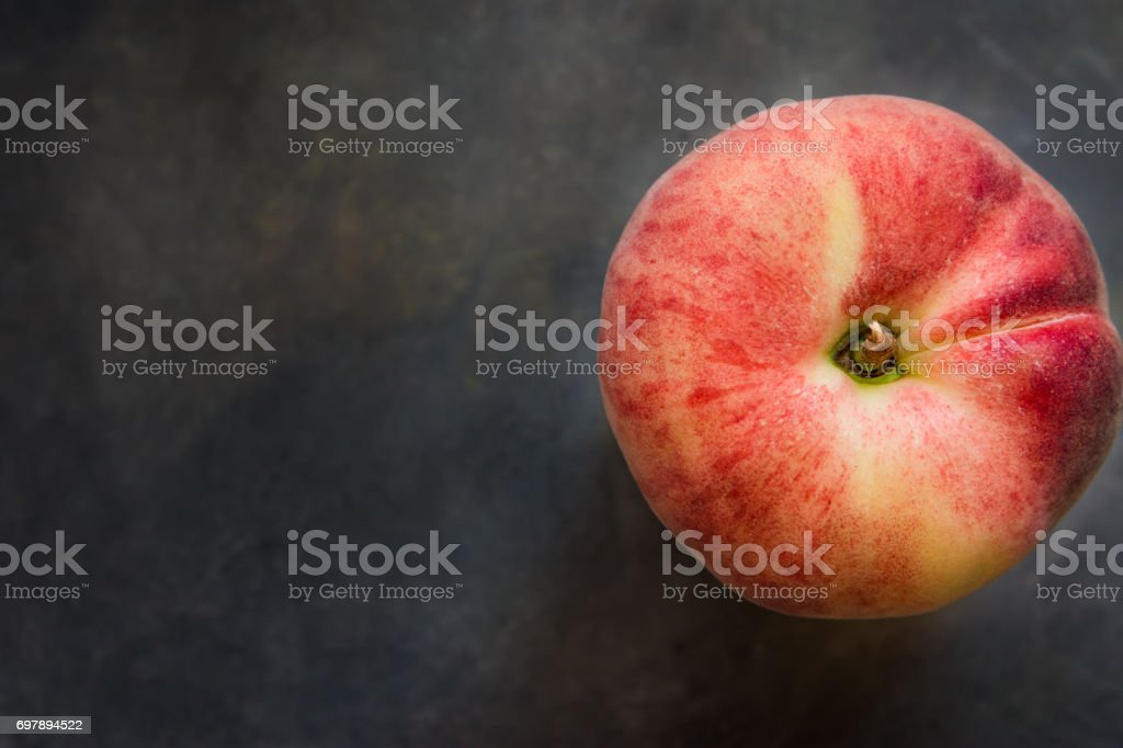 Ripe colorful red saturn peach on dark concrete background, top view, copy space, conceptual image stock photo