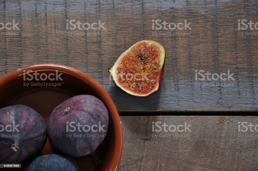 Ripe figs in bowl on wooden table stock photo