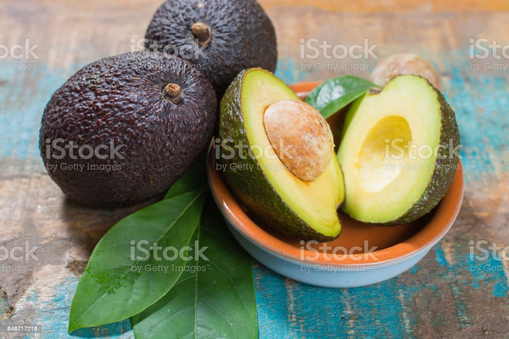 Ripe fresh avocado with leaves on blue wooden table stock photo