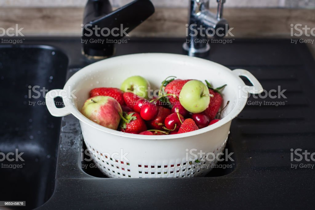 Ripe Fresh Berries and Fruits in black kitchen-sink. Summer Food Concept royalty-free stock photo