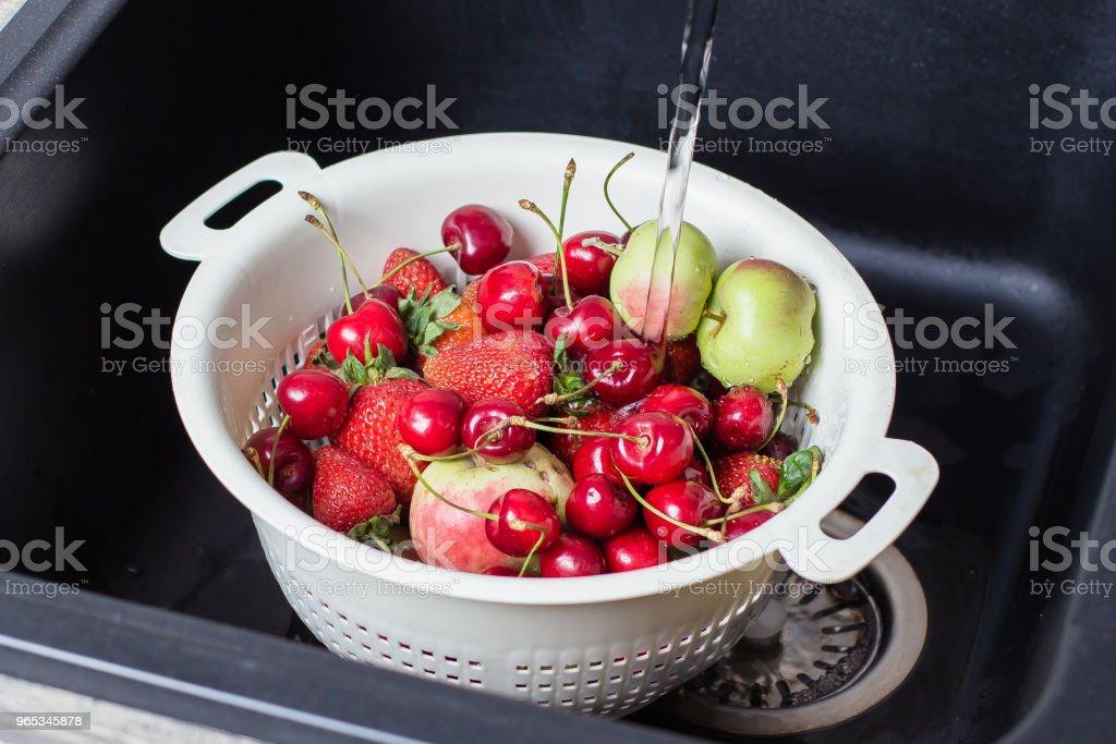 Ripe Fresh Berries and Fruits in black kitchen-sink under stream water. Summer Food Concept zbiór zdjęć royalty-free