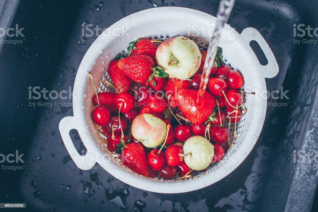 익은 신선한 열매 그리고 스트림 물 아래 검은 부엌 싱크대에 과일. 여름 음식 개념 - 로열티 프리 가방 스톡 사진