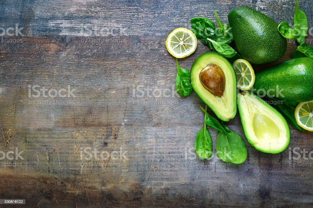 Ripe fresh organic avocado with spinach leaves and lemon slices. stock photo