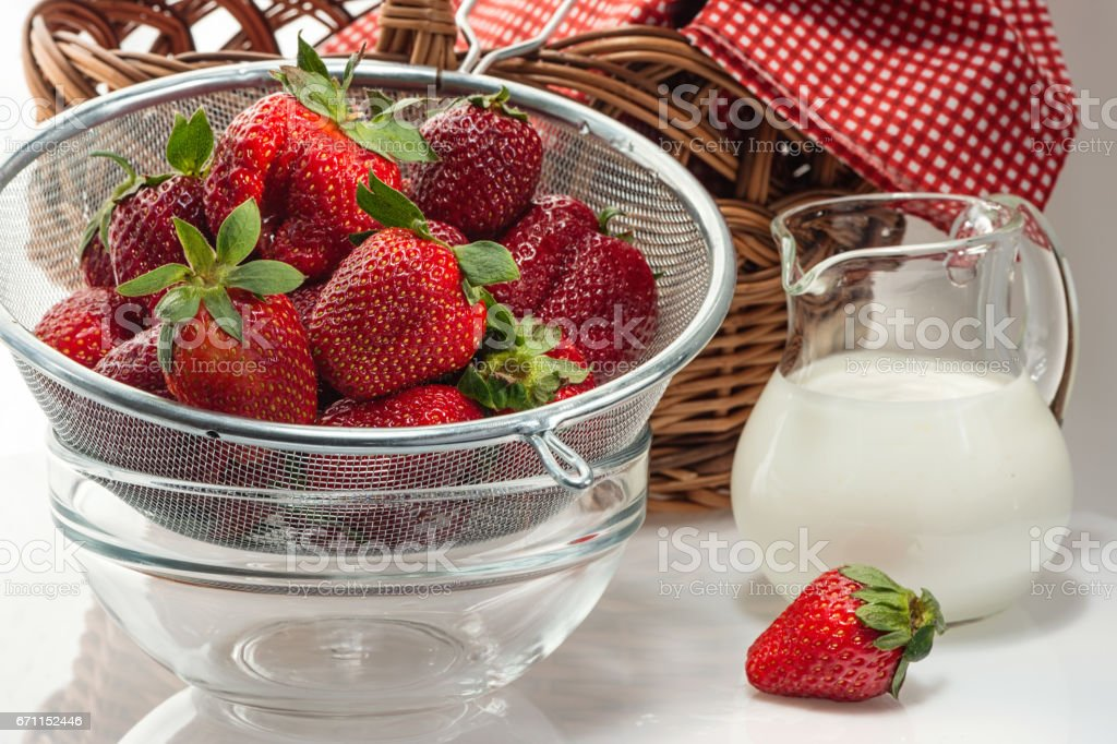 Ripe fresh strawberries in colander and cream in jug стоковое фото