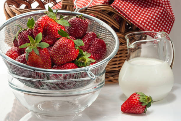 Cтоковое фото Ripe fresh strawberries in colander and cream in jug
