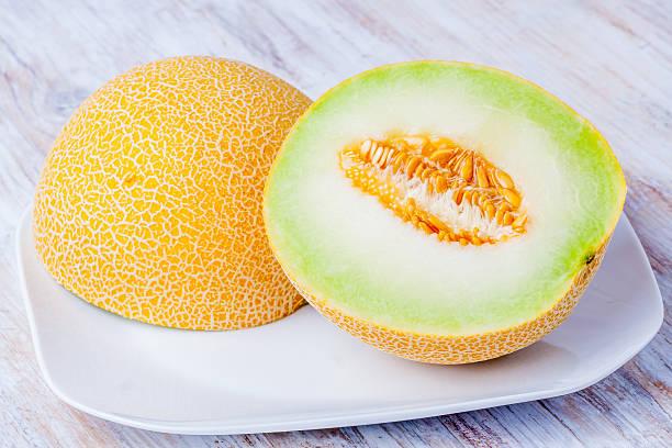 Ripe Galia melon and its slice on plate stock photo