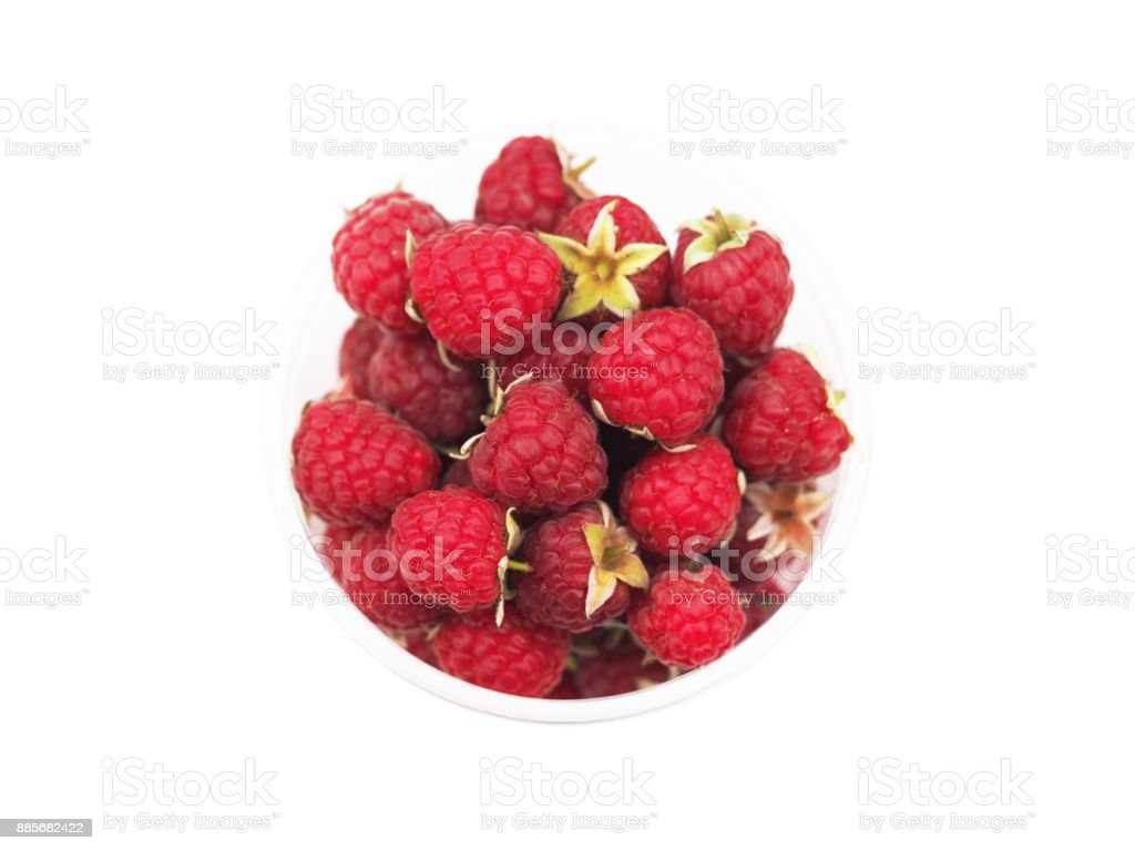 Ripe garden raspberries on stems in a clear plastic cup isolated on a white background. Rubus idaeus (raspberry, also called red or European raspberry) is a red-fruited species of Rubus. Top view stock photo