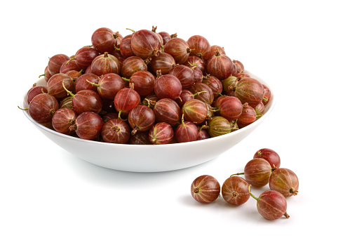 ripe gooseberries in a plate close-up on a white background, horizontal view
