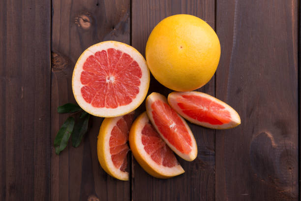 Ripe grapefruit slice on brown wooden background stock photo