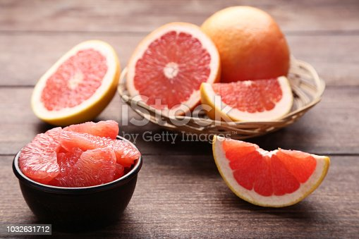 Ripe grapefruits in basket and bowl on brown wooden table