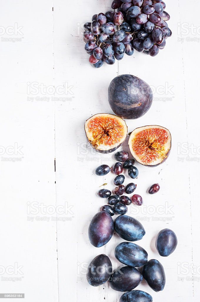 Ripe Grapes, plums and Figs on white wooden table royalty-free stock photo