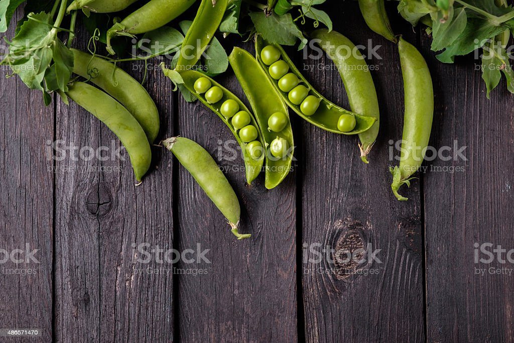 Ripe Green peas on wooden table. stock photo
