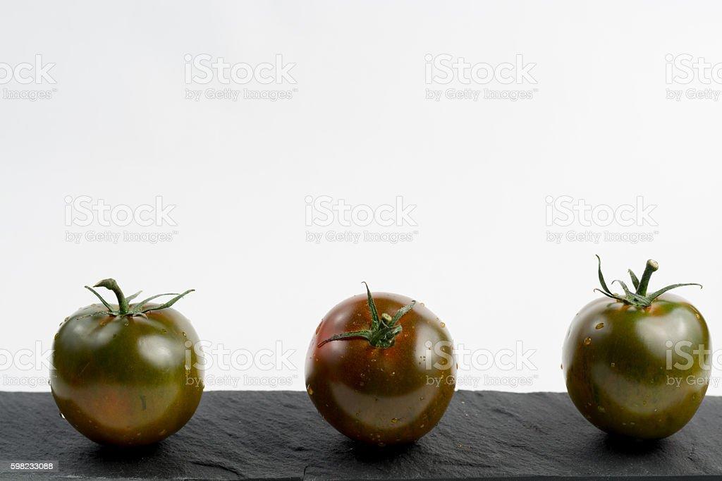 Ripe green-brown kumato tomatoes on black stone stock photo