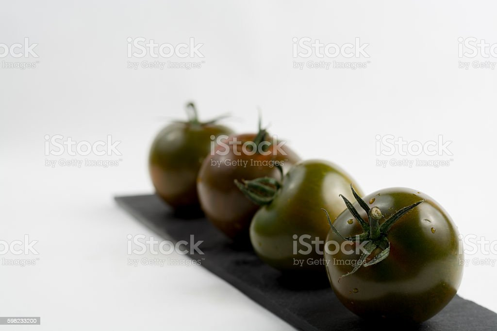 Ripe green-brown kumato tomatoes on black stone foto royalty-free