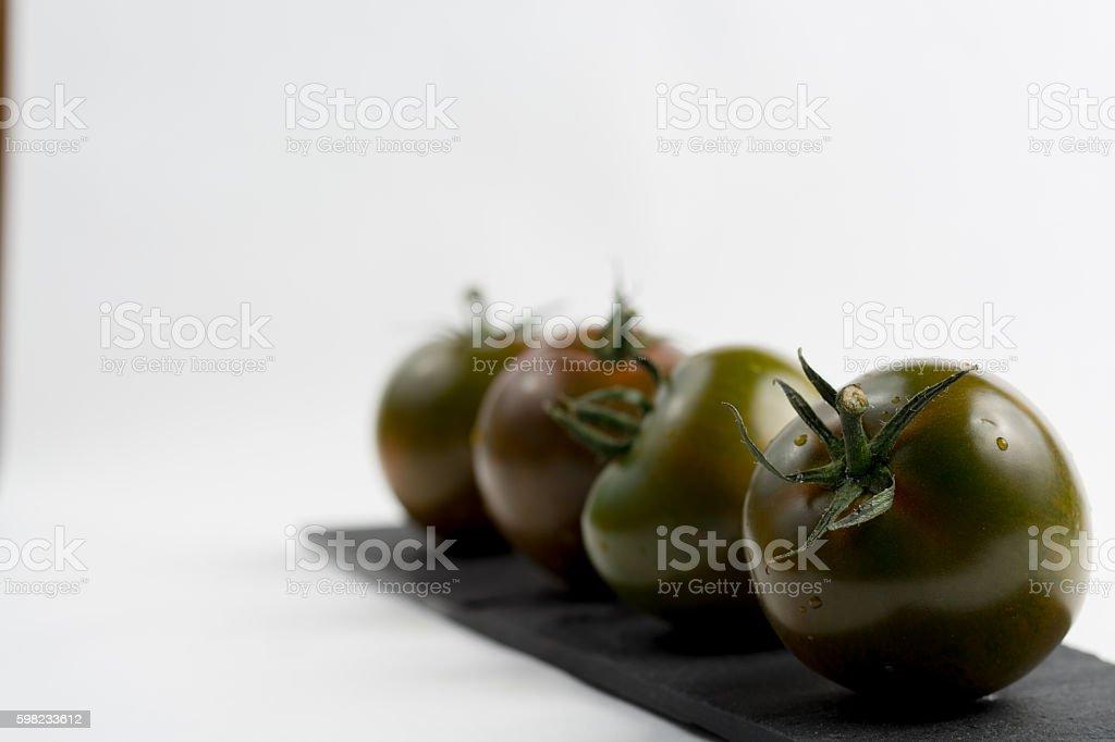 Ripe green-brown kumato tomatoes on black stone foto royalty-free