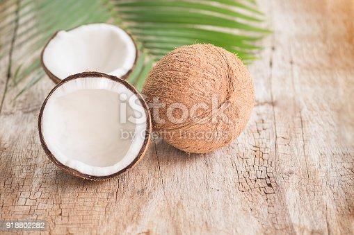 istock Ripe half cut coconut on a wooden background. Coconut cream and oil. 918802282