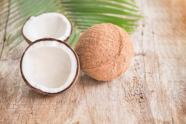 Ripe half cut coconut on a wooden background. Coconut cream and oil. stock photo