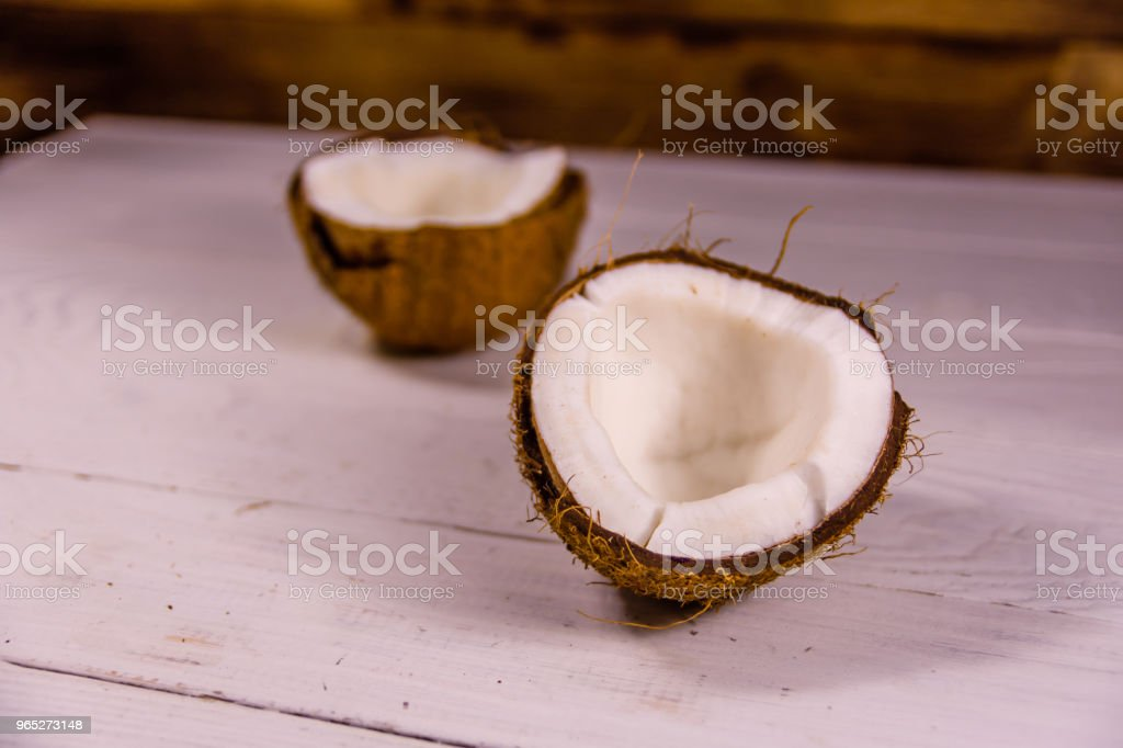 Ripe halved coconut on a wooden table royalty-free stock photo