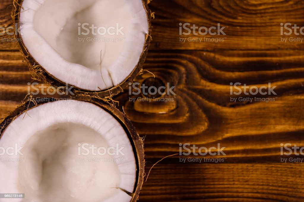 Ripe halved coconut on a wooden table. Top view royalty-free stock photo