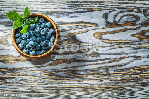 Ripe huckleberries in round wooden bowl.