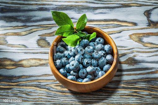 Ripe huckleberries in wooden bowl top view.