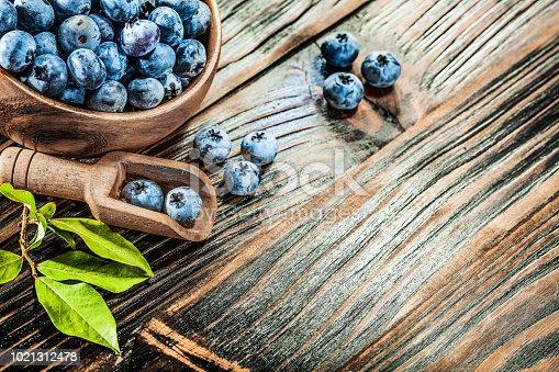 Ripe huckleberries in wooden spoon bowl.