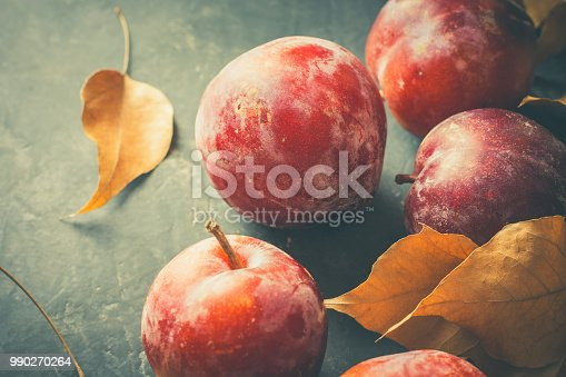 istock Ripe Juicy Big Red Plums Dry Yellow Orange Leaves on Black Stone Background. Autumn Fall Composition. Vibrant Colors. Flat Lay. Harvest Thanksgiving Poster Card Template. Vintage Style Toned 990270264