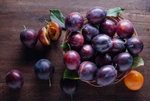 Ripe juicy plums on a wooden background. stock photo