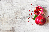 Ripe juicy pomegranate fruit on white wooden rustic background. top view