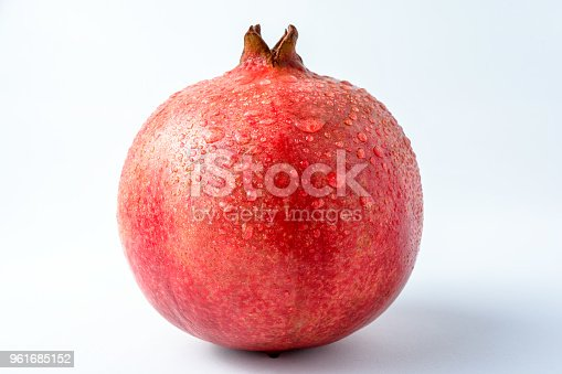 ripe juicy pomegranate in droplets of water. Isolated