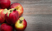 Ripe juicy red apples close up on wooden table. Top view. Copy space