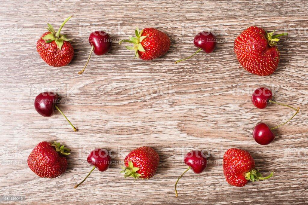 Cerise rouge juteuse mûre et une grosse fraise rouge se trouvant sur un fond en bois. Baies d'été douce. Poser de plat. vue de dessus. Châssis de baies, fond. photo libre de droits