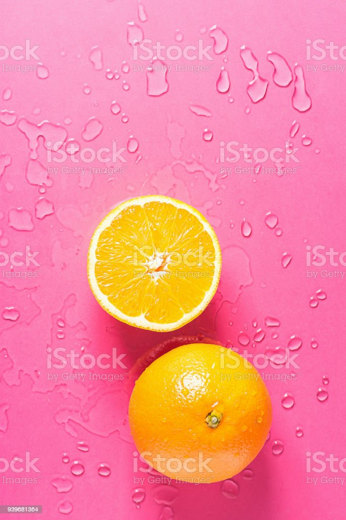 Ripe Juicy Whole and Halved Orange on Fuchsia Pink Background with Water Drops. Vitamins Healthy Diet Summer Detox Vegan Superfoods Concept. Poster Banner Template. Copy Space Flat Lay stock photo