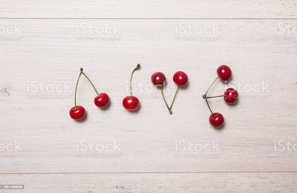 Ripe juicy yellow-red cherry on wooden background. Word love laid out cherries. Ripe summer fruit. royalty-free stock photo