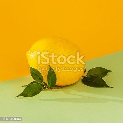 Ripe lemon with a leaf close up on bicolor multicolored background. Juicy summer vitamin C, citrus minimal concept.