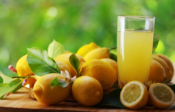 ripe lemons and juice cup on table ripe lemons and juice cup on table lemon juice stock pictures, royalty-free photos & images