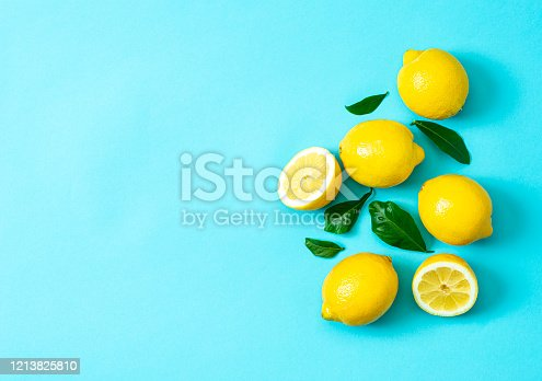 Ripe lemons flat lay with leaves on blue background. Copy space, top view