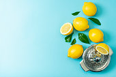Ripe lemons flat lay with leaves on blue background.With one citrus juicer Copy space, top view