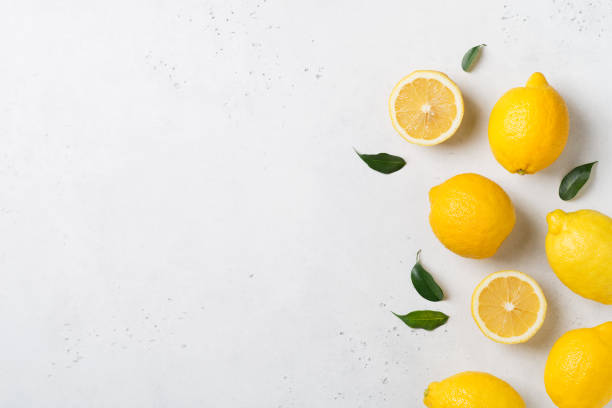 ripe lemons flat lay with leaves on white background - agrume foto e immagini stock