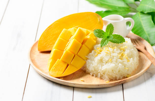 ripe mango and sticky rice with coconut milk on white wood background, - sticky stock pictures, royalty-free photos & images