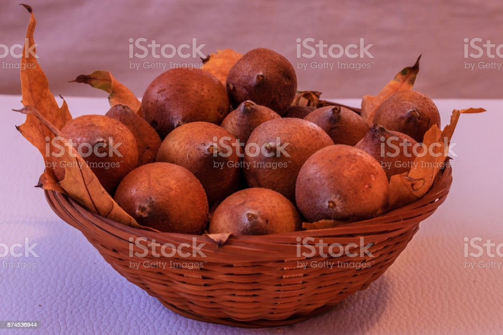 Ripe medlar and yellow leaves in wooden basket on white background,close up stock photo