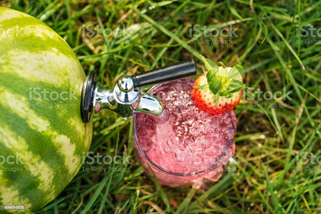Ripe melon sitting in the grass with a tap fitted stock photo