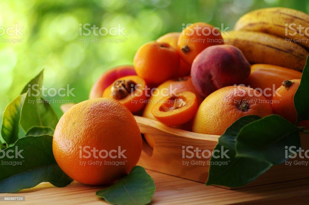 ripe orange and various fruits on wooden basket stock photo